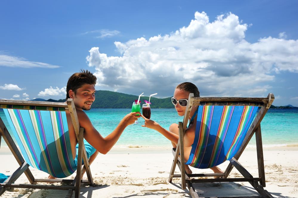 мужчина и женщина пьют коктейли на пляже