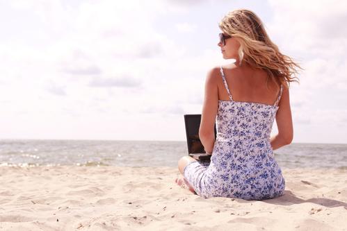 женщина на пляже с ноутбуком