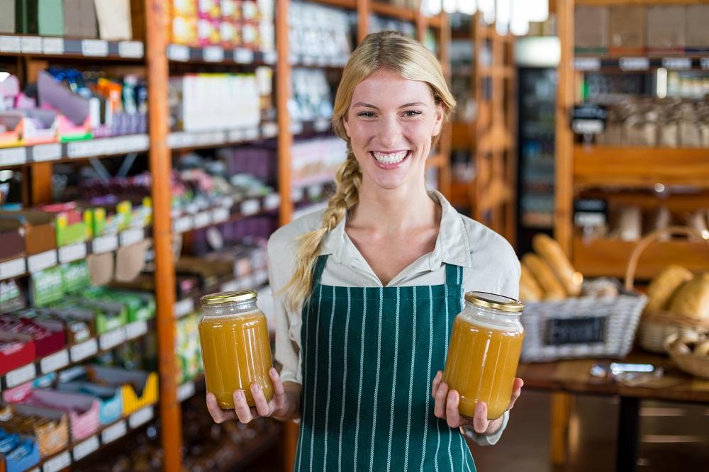 Женщина держит банки с медом