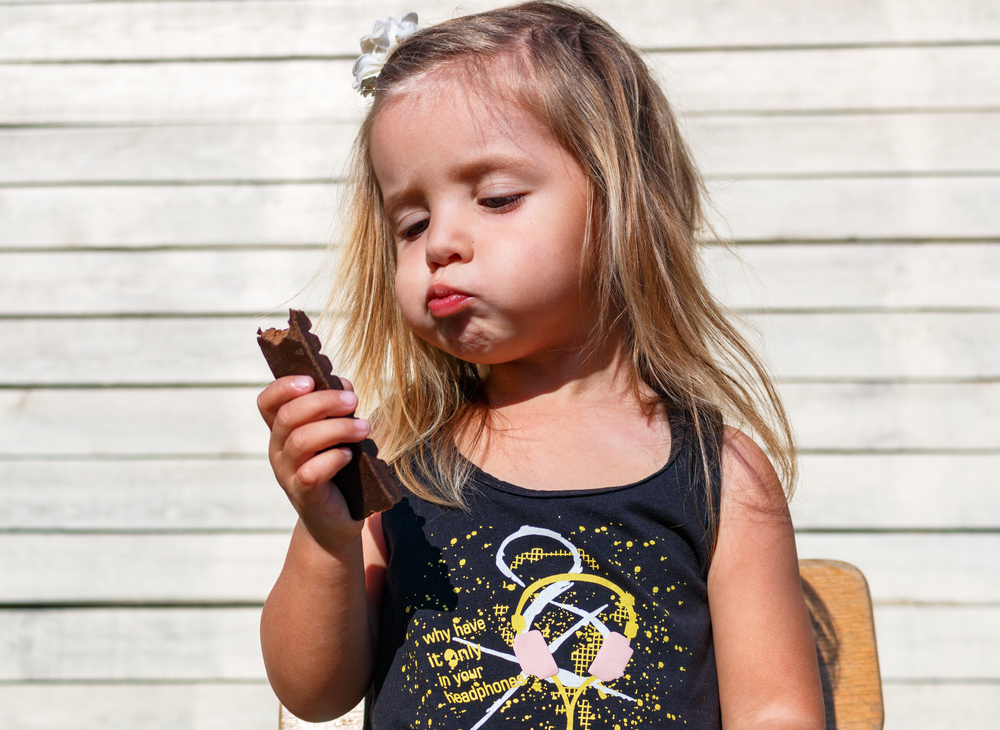 ребенок ест конфету