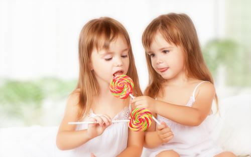 девочки едят леденец